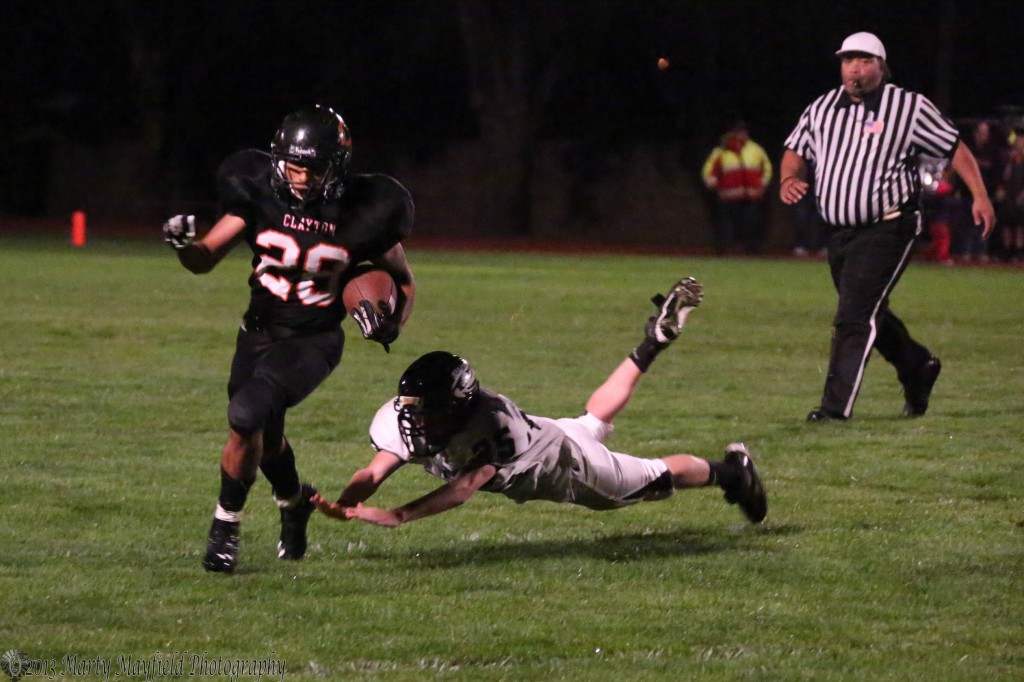 Brian Montoya slips past a Raton tackler in the second quarter of the game Friday night in Clayton