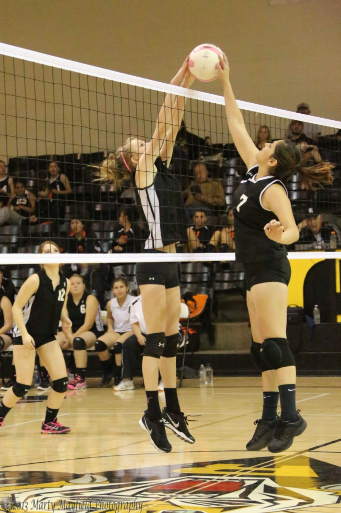 Alina Pilmore makes the block as a Taos player attempts to bat it over the net.