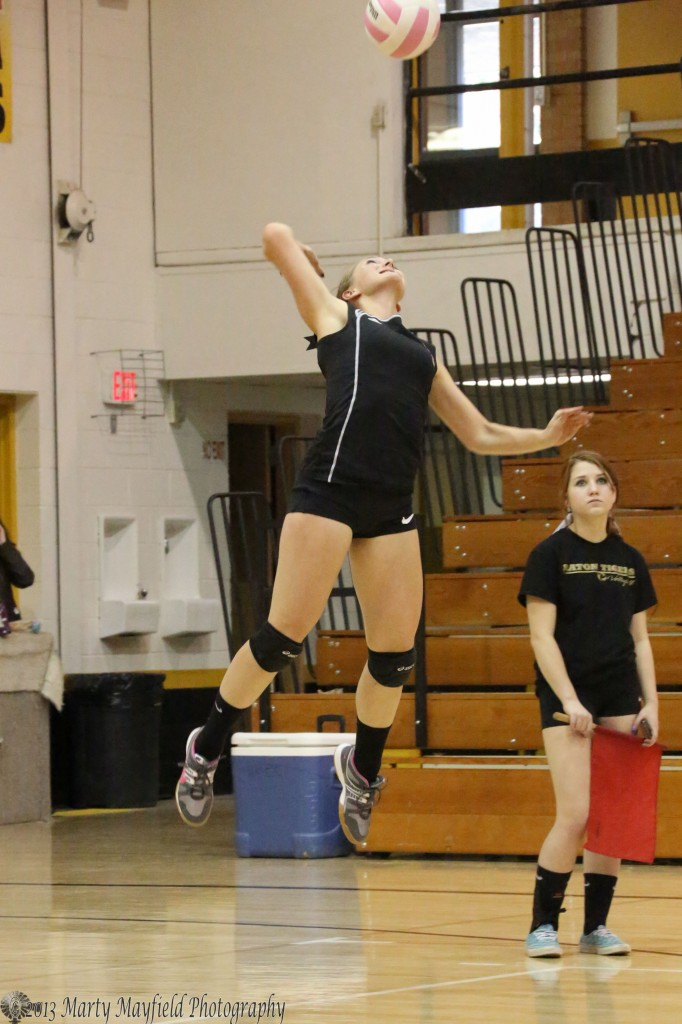 Mikala Vewrtovec goes high as she serves the ball during the Taos match in Tiger Gym as Tate wood looks on from her position from the corner
