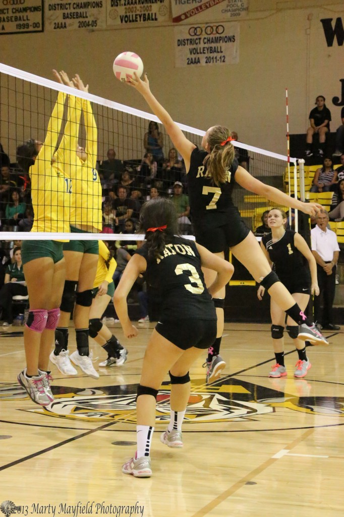 Kayanna Spaulding (12) and Reyna Trujillo (9) meet at the net as Mikala Vertovec tips the ball up and over.