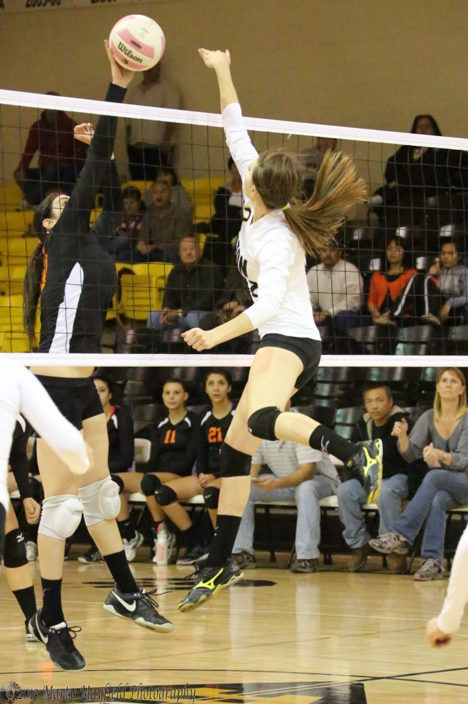 Kristina Jansen makes the kill while Bertha Vigil makes the one handed block.