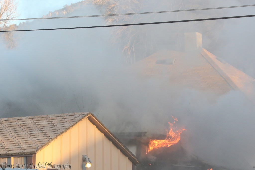 Flames can be seen from the front porch of the house at 830 N 3rd St in Raton.