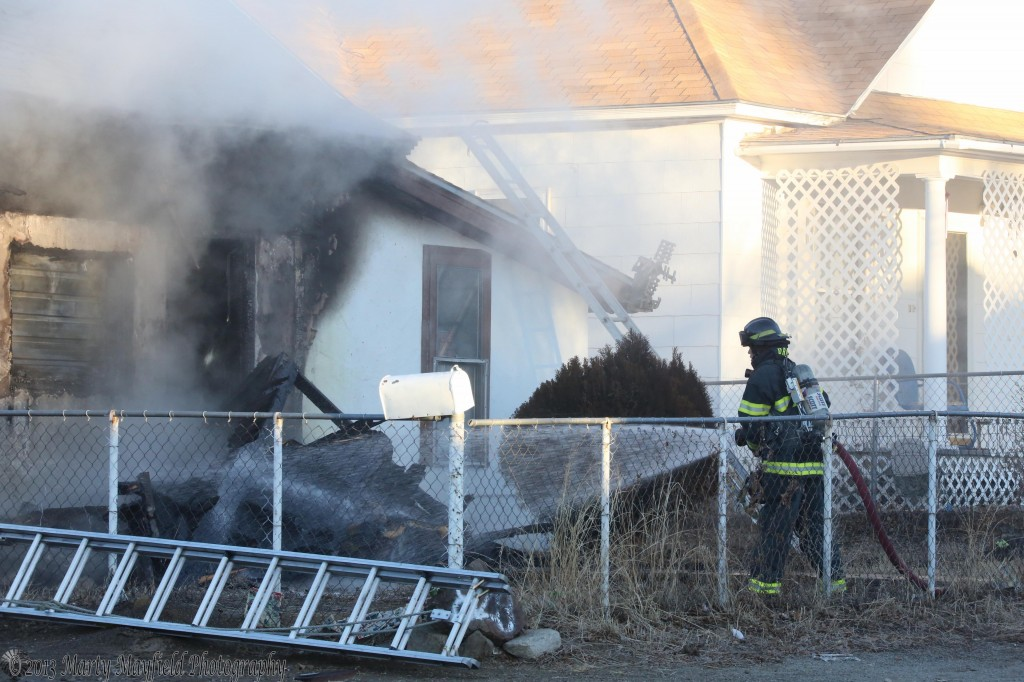 A Raton Fire Fighter sprays water on the fallen front porch of the house at 830 N 3rd in Raton, NM.