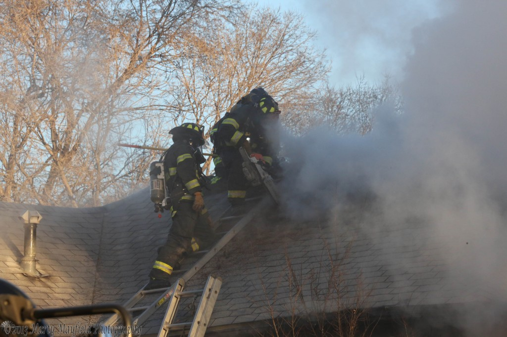 Fire Fighters expose the attic of the house at 830 N 3rd Friday morning as they battle a house fire.