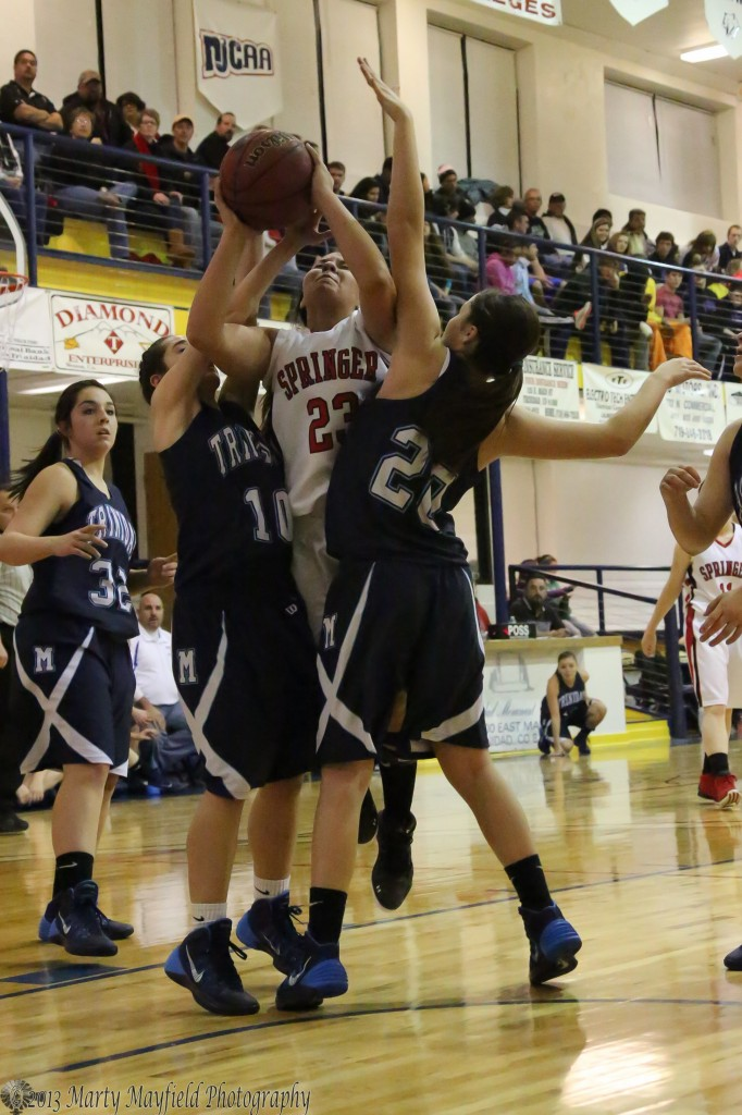 Springer's Cordy Tafoya threads her way through Miners Kayla Garrison and Christa Rhoads Saturday evening during the girl's Championship game of the TSJC Invitational