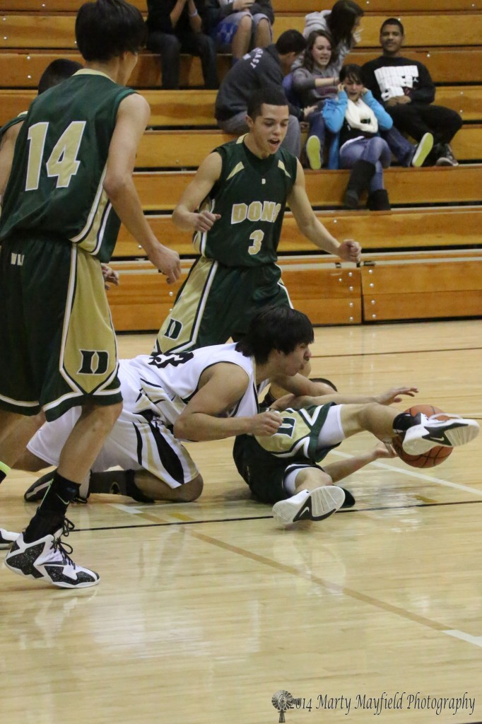 Raton's Anthony Brown scrambles for the ball as it gets loose Thursday evening in Tiger Gym