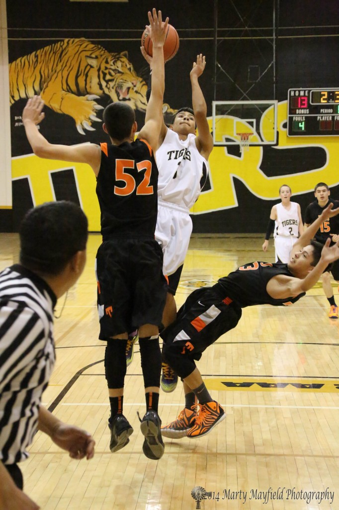 Jonathan Cabrieles drives the lane as AJ Fresquez goes for the block and Johnny Martinez finds his way to the floor.