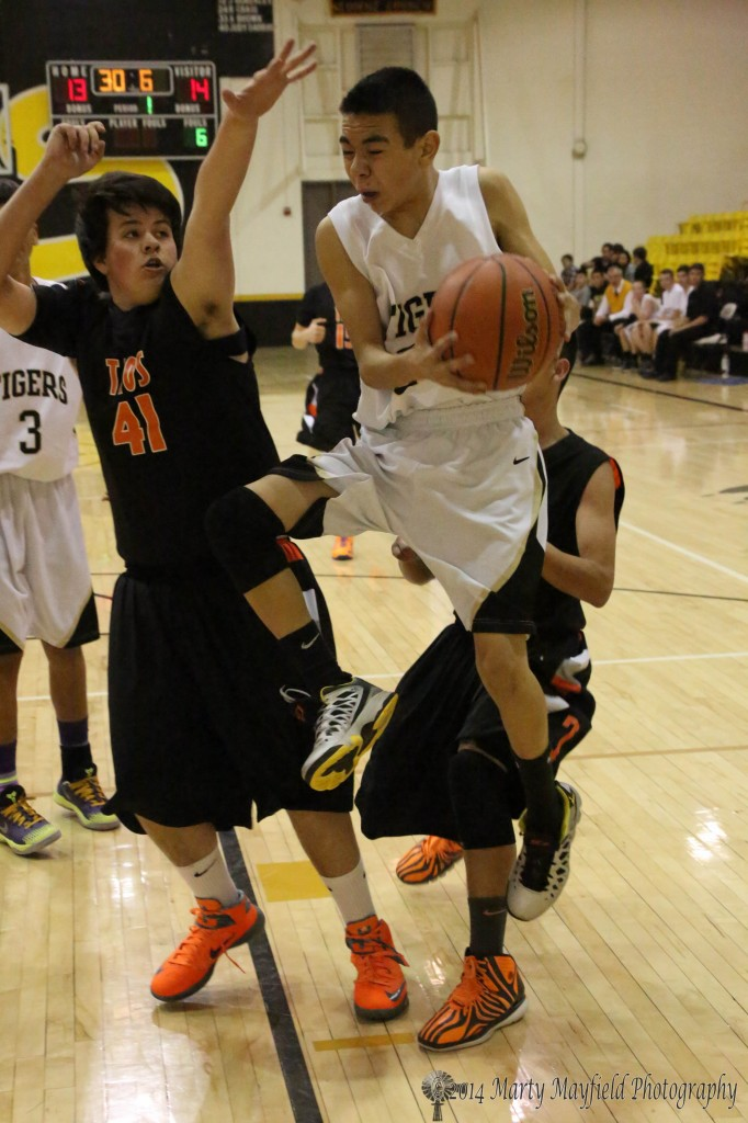 Jesse Espinoza drives the lane again late in the first quarter as Luke Dickinson works for the block during the JV game Saturday night in Tiger Gym