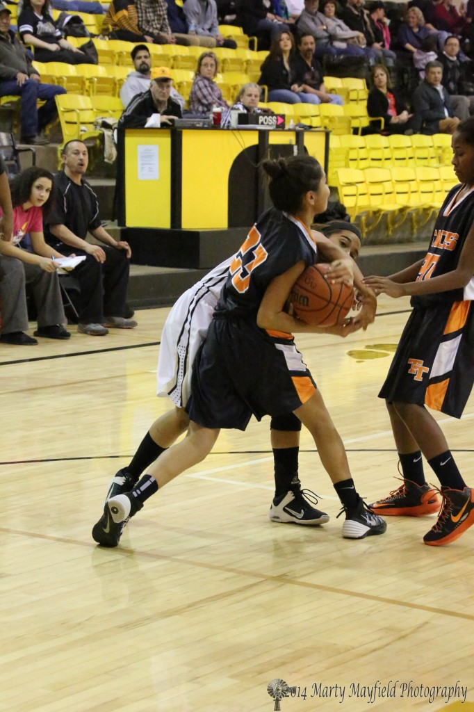 Joni Brown tangles with Elicia Sanchez for the ball during the JV game with Taos Friday night in tiger Gym.