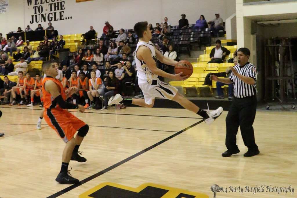 Luis Ruiz makes the save during the varsity game in Tiger Gym Saturday night against Taos.