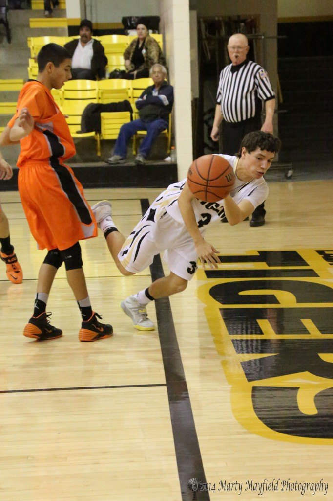 Dylan Query goes for the save Saturday evening during the varsity game in Tiger Gym against Taos.