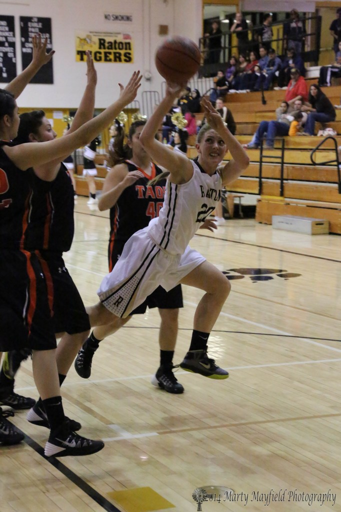 Mikala Vertovec trips through a tangle of Taos ball players as tries for a shot Friday night in Tiger Gym