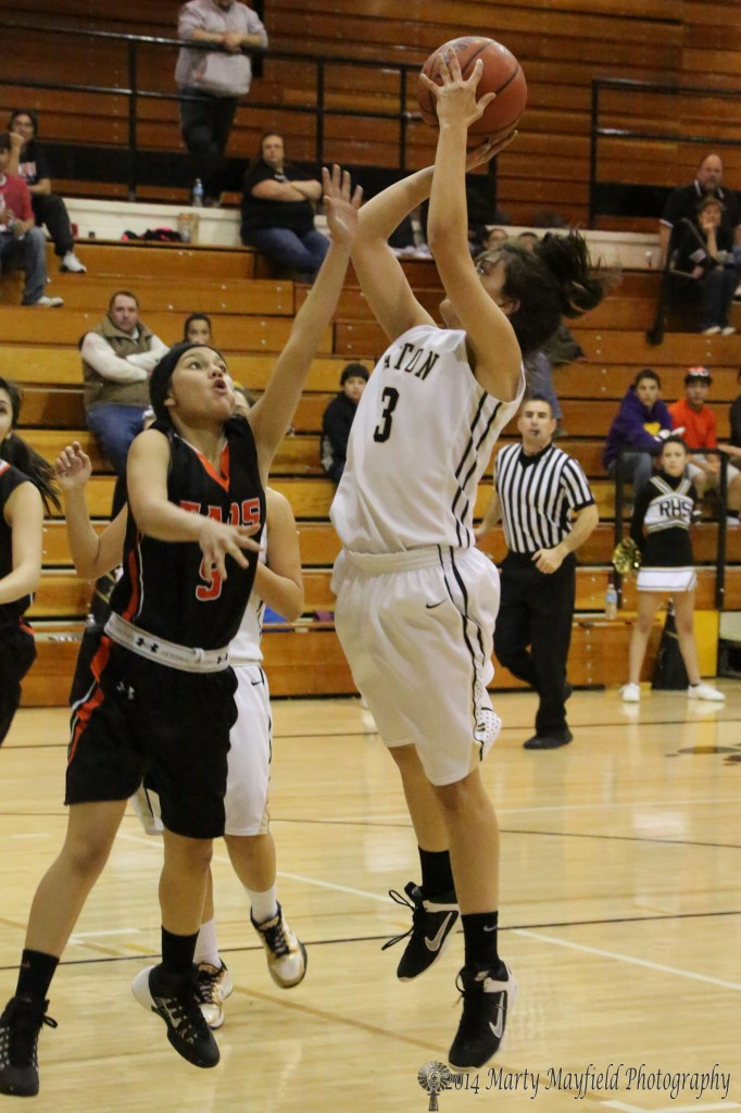 Shania Dorrance gets the jump on Elena Espinoza for the short jumper Friday night during the varsity game in Tiger Gym
