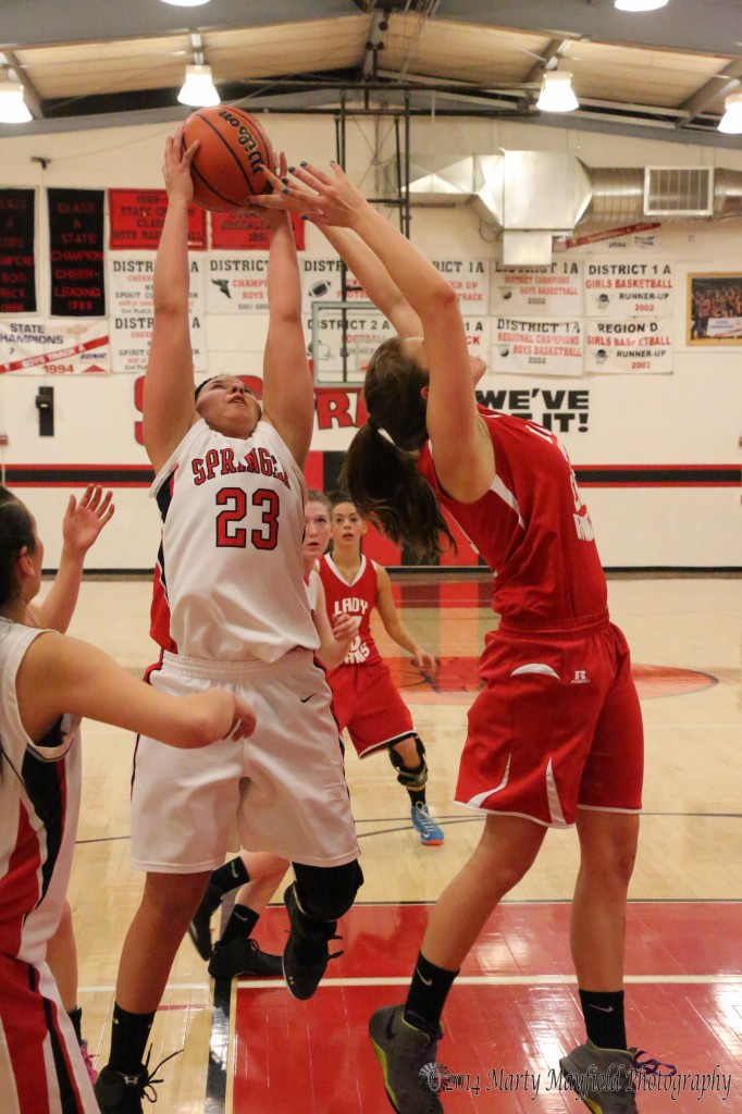 Cordy Tafoya (23) and Gentry Haukabo go for the rebound during the district championship game in Springer Friday night