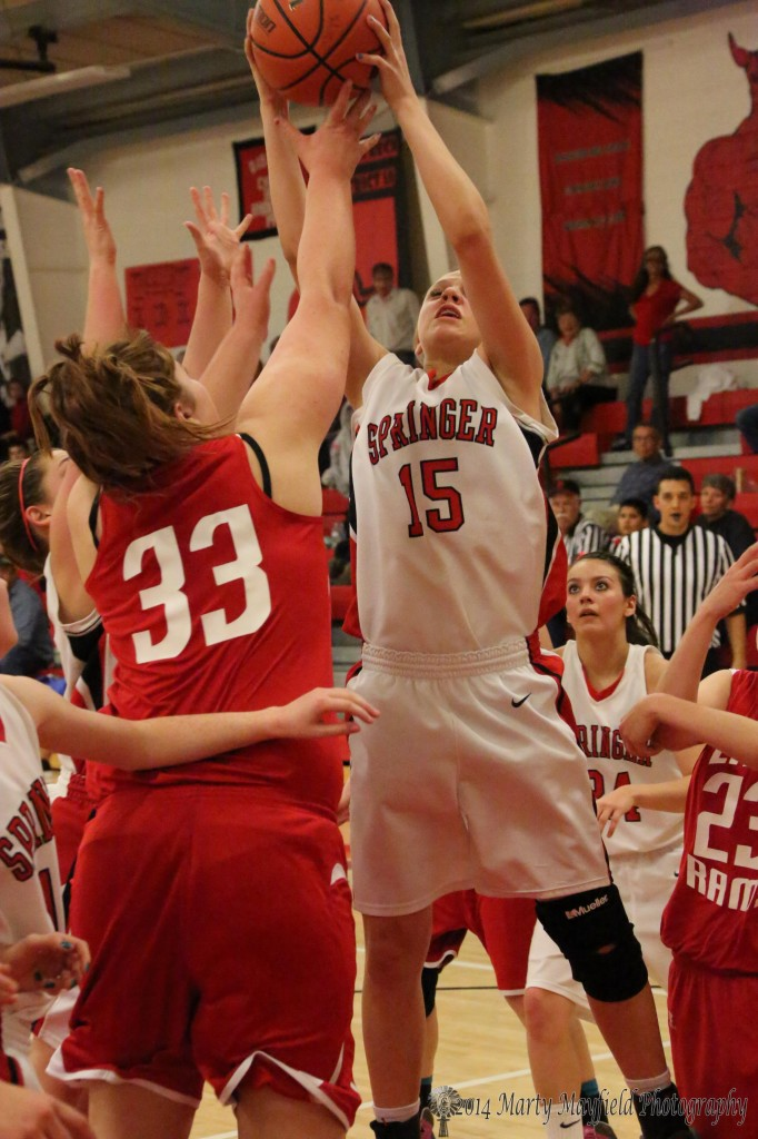 Danielle Blake and Mariah Vanderlie scramble for the rebound Friday night in Springer for the district championship game