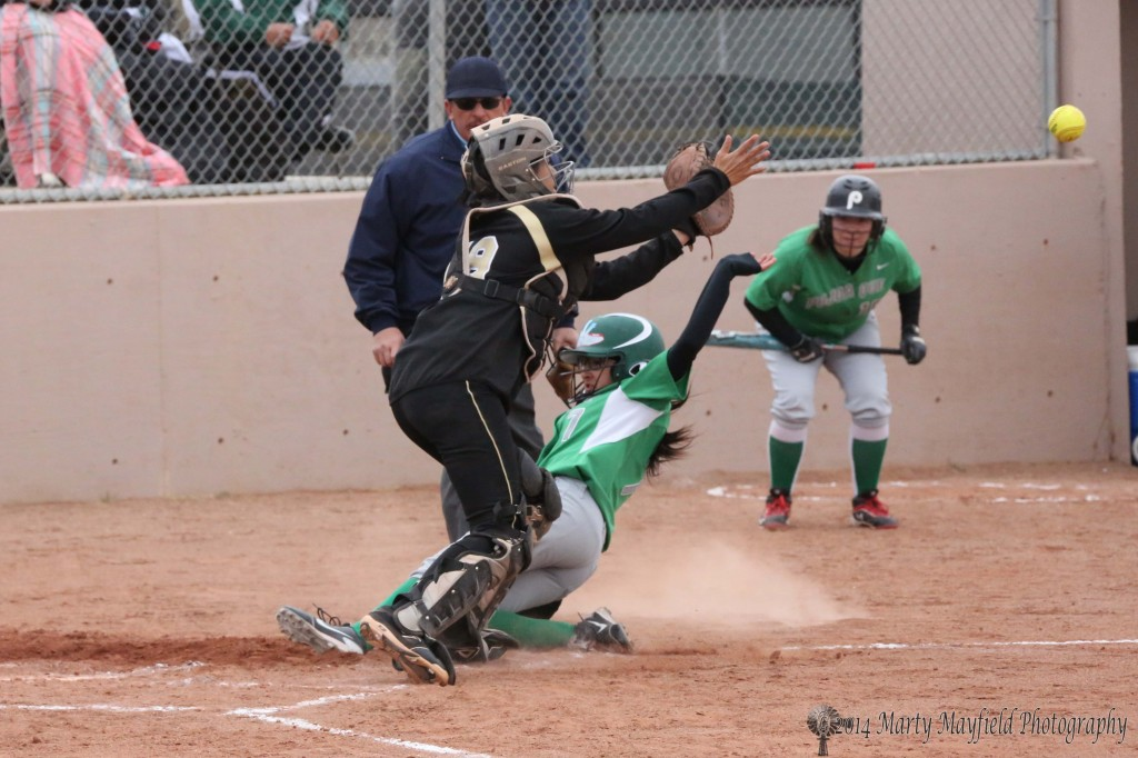 Analisa Lovato beats the ball home as she slides into home plate for one of Pojoaque's runs that would eventually tie the game in the fifth inning.