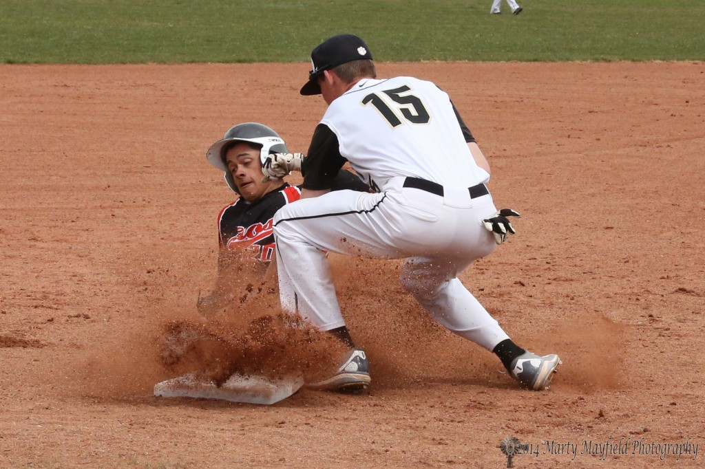In a cloud of dust the Taos player is called out as Cam Baird makes the play at third.