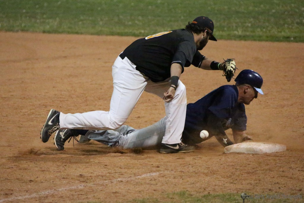 Chris Williams drops the ball as he goes for the tag at first base late in the game Wednesday evening