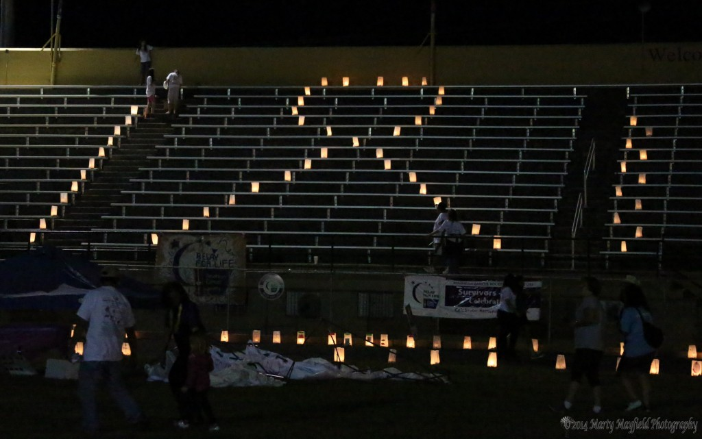Luminarias line the track and make a ribbon in the stands.