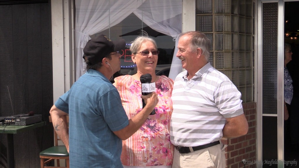 Hal and Laura Brewer visit with KRTN's Billy Donati after cutting the ribbon to officially open the Patchwork Phoenix on Raton's historic first street.