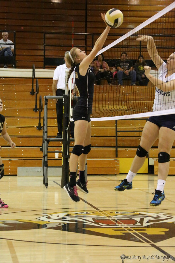 Alina Pillmore goes up for the block, but the ball gets off to the side during the varsity game