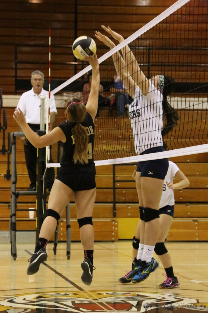 Montana tips the ball while Lady Miner Cory LaFon goes for the block