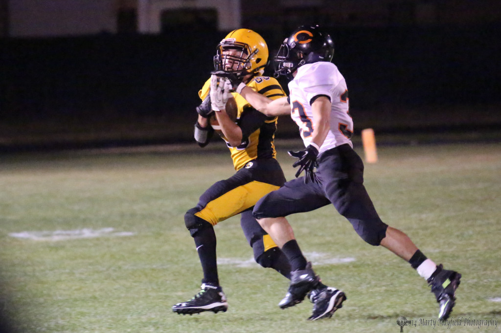 Martin Ortiz hangs on for a 40-yard pass play as Jose Zamora gets a hand in.