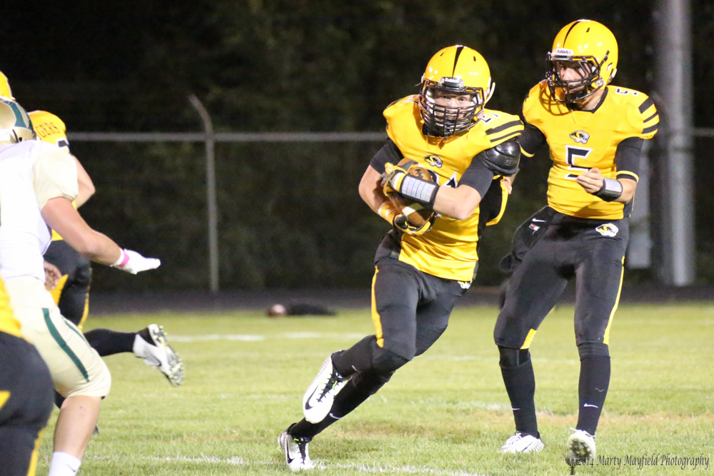Dakota Martinez takes the hand off from Raton QB Dante Mileta and heads around the for positive yardage.
