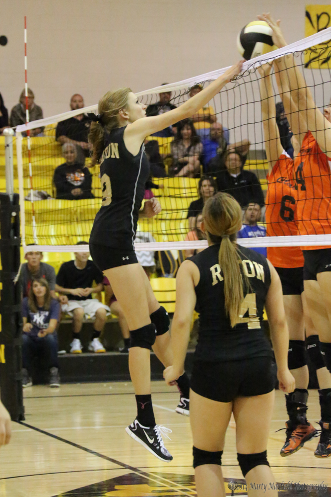 Alina Pillmore sends it over the net as Mitzi Vital (6) and Brittany Thelander (14) go for the block