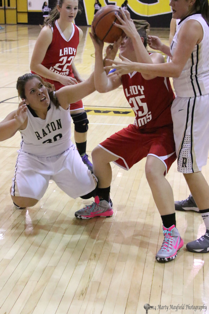 Raton's Sydni Silva and Lady Ram Jessica Pittman tangle for the ball during the varsity game in Raton Thursday evening