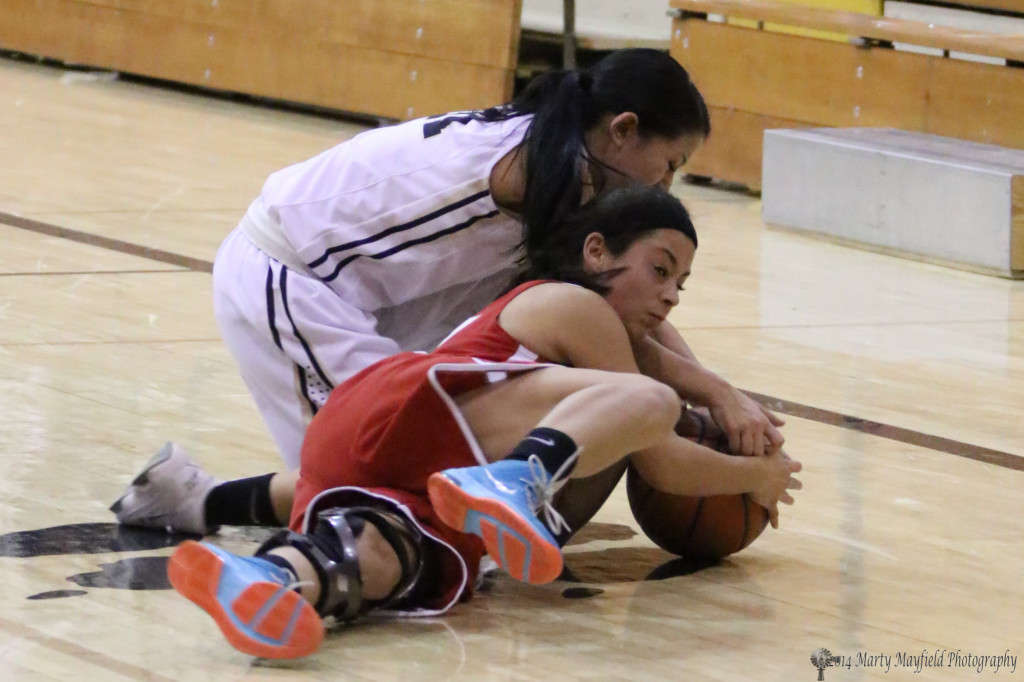 Tausha Ortega and Lady Ram Salina Rael go for the loose ball during the varsity game Thursday evening.