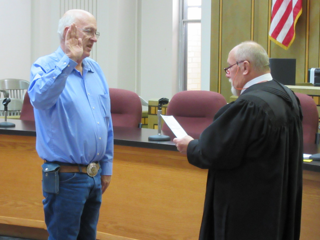 Colfax county Commissioner Bill Sauble takes the oath of office Monday afternoon from District Judge John Paternoster