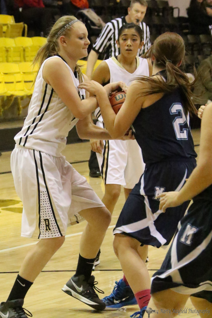 Ivy Fernandez and Brittnee Coberly tussle for the ball during the Raton Trinidad game in tiger Gym Tuesday night.
