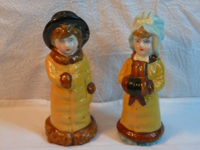 "These shakers are more than a hundred years old. They were part of the merchandise that popped up emulating a ""Kate Greenaway"" design. Kate Greenaway was a children's book illustrator and author who lived during the late 19th century.  Many of her book characters were Victorian children sporting outfits of frilly smocks, mob caps and sunbonnets."