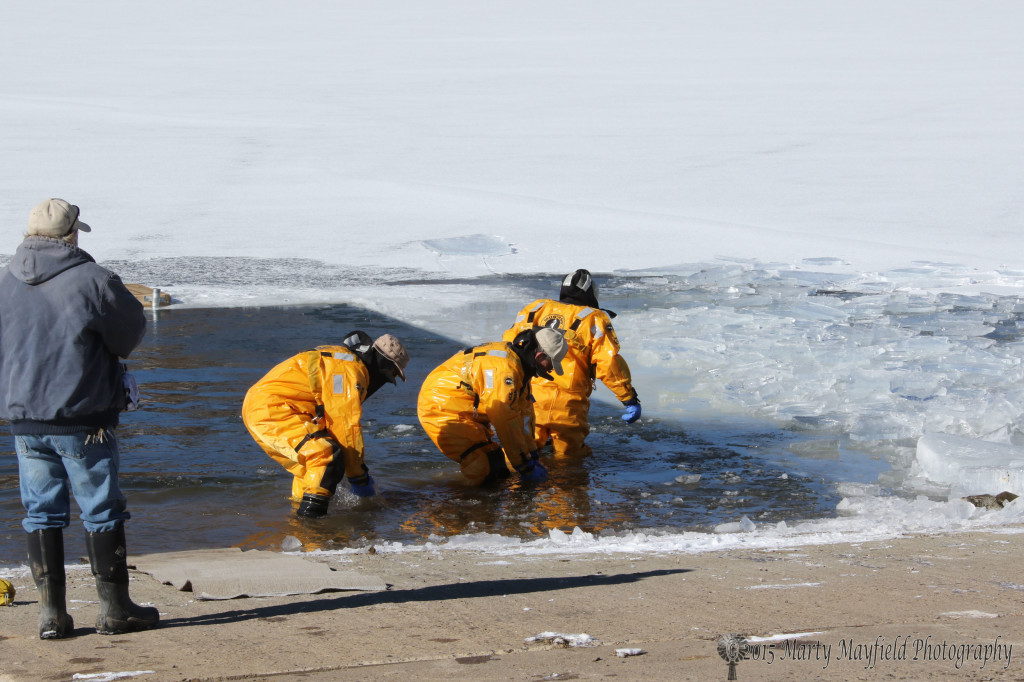 Bob McIvor, David Gurle and Rick Martin clear some of the new ice buildup before the 2015 Polar Bear Plunge at Lake Maloya Thursday afternoon.