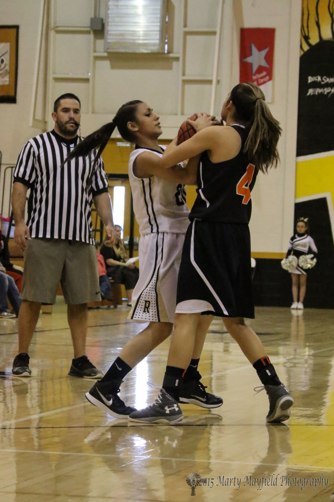 Lady Tiger Daisy Earle and Bri Fong tie up the ball Friday afternoon in Tiger Gym during the last home game of the season.