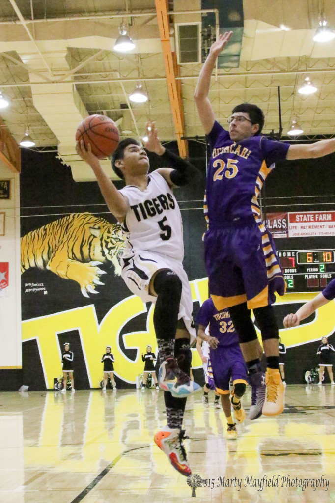 Austin Jones (5) goes for the basket as John Paul Garcia (25) goes for the block Saturday night in tiger Gym