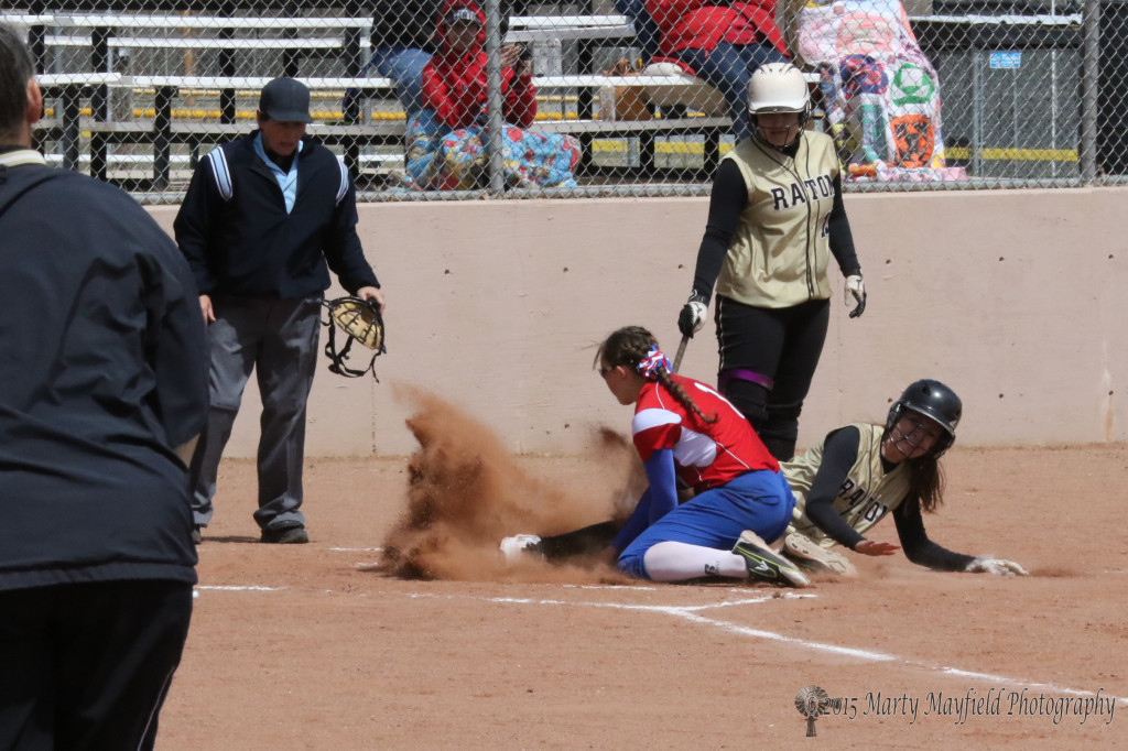 Mariah Encinias slides into home plate as Leanne Calhoon tags her out