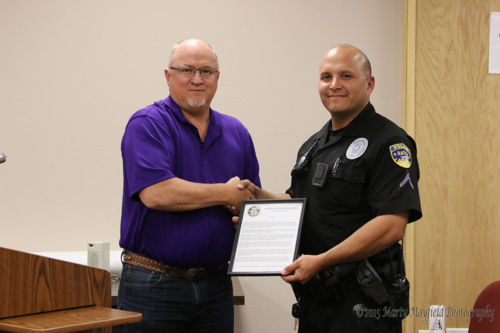Officer Cory Coca accepts the recognition letter for Aros Raton's Police Service Dog in recognition of his long service to the department.