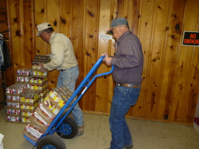 Verner Query and David Wingo are storing some of the unloaded food.