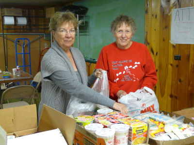 Rosalie Block and Dorothy Kay are assembling the bags of groceries.