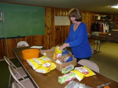 Naomi Winders is making up small bags of rice for distribution in the food bags.