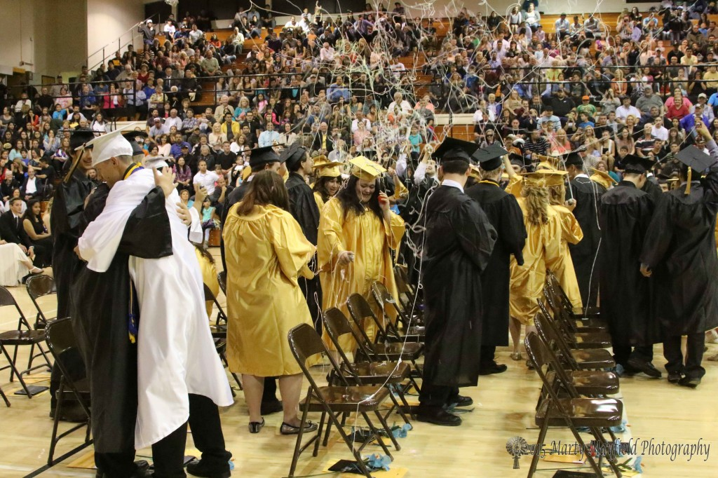 The silly string flies as the graduates move to the middle of the floor after their official sign of graduation, the turning of the tassel, was performed