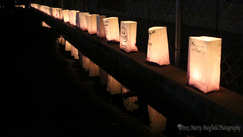 Puddles left behind by the rain earlier that evening reflects the many luminaria that line the track at Tiger Stadium Friday evening during the 2015 Relay for Life