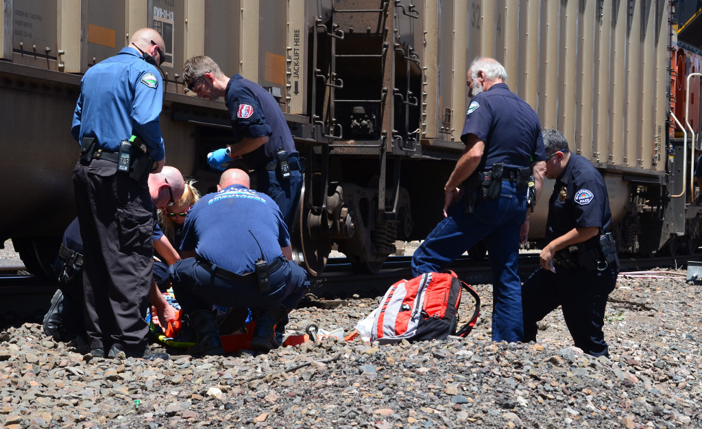 MAN VS. TRAIN- Huerfano emergency service first responders come to the aid of a man who thrw himself in front of a train Wednesday, July 22.  The man is recovering from his failed suicide attempt, according to officials this week.  Photo by Eric Mullens.