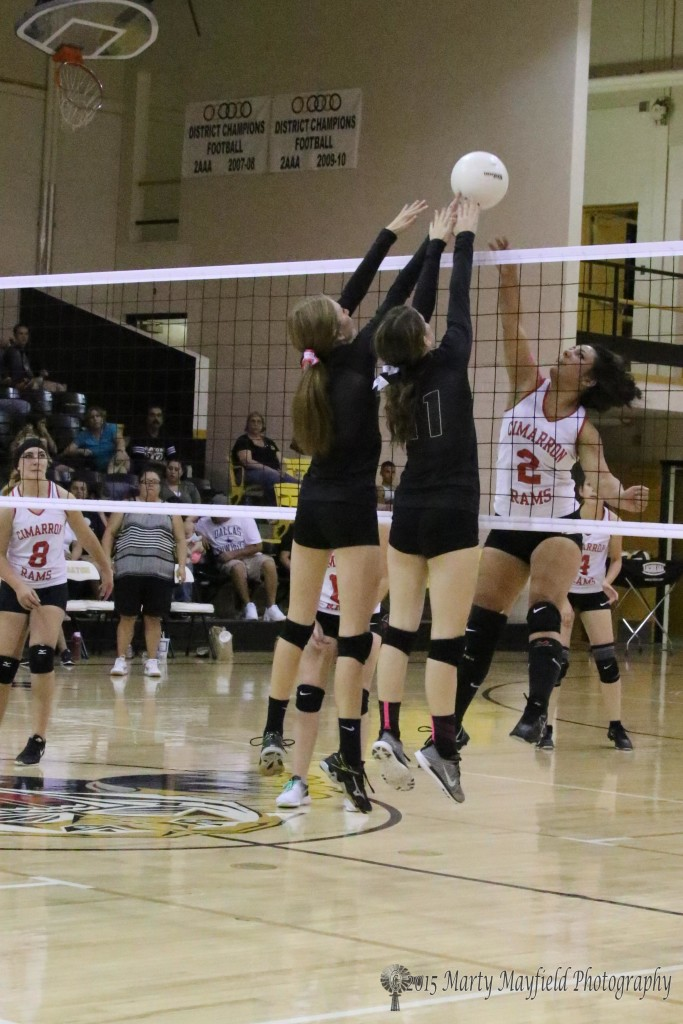 Mariah Martinez hits the ball as Alina Pillmore gets a finger tip on it along with Camryn Mileta