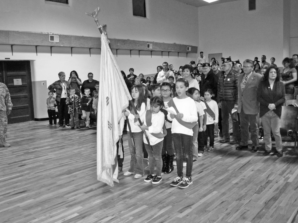 Springer's newly formed Girl Scout troop performed the posting of the flags ceremony at the Veterans Day celebration at the Luna College auditorium last week. Presenting the flags are:  Jordan Romero with US flag, Esperanza Tafoya with Zia flag and Brenna Duran calling the commands.  Photo by Sherry Goodyear.