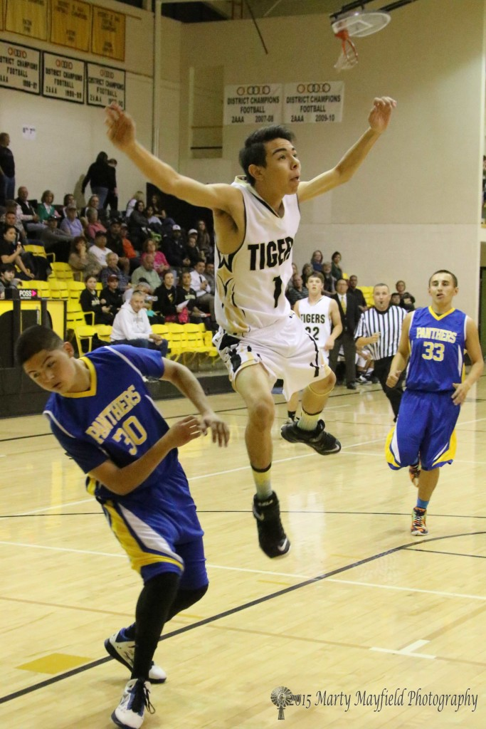 Jesse Espinoza(1) flies by Ernie Lopez (30) on his way toward the basket Tuesday evening at Tiger Gym.