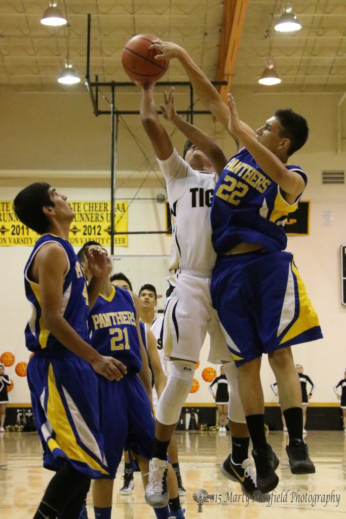 Auston Jones goes for the short jumper as Aaron Archuleta gets fingers on the ball and makes the block.