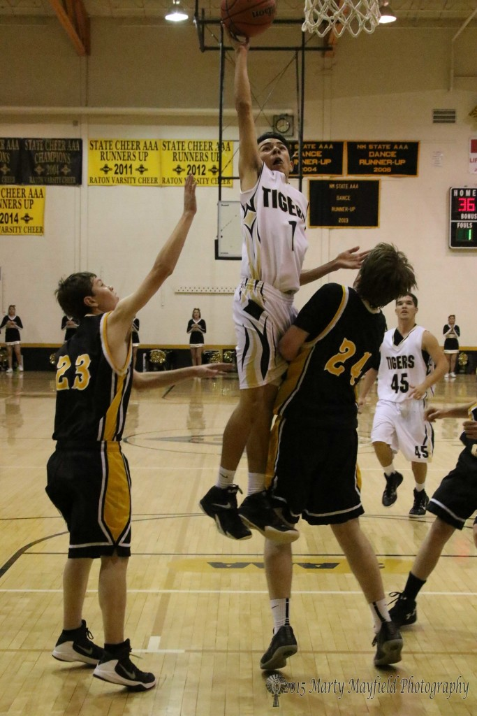 Jesse Espinoza flies between Hayden Briesh (23) and AJ Wright (24) on his way to the basket in the second quarter.